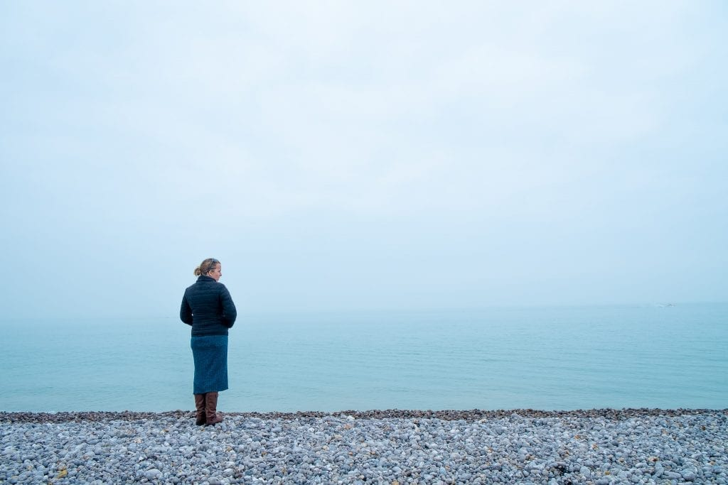 Nathalie standing on the pebble beach of Fecamp, enjoying the meditative force of the sea and the pebble beach