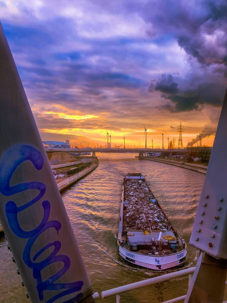 HDR Photo of a cargo ship passing under a bridge at sunset in the Port of Antwerp